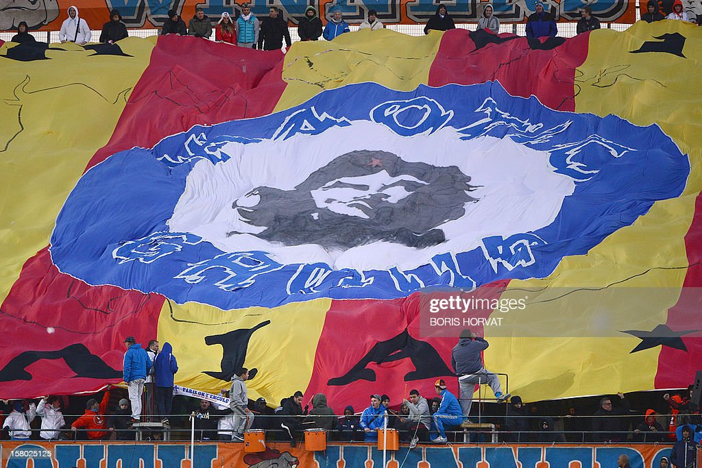 Marseille supporters display a giant flag during the French L1 football match between Olympique de Marseille (OM) and Lorient (FCL) at the Velodrome stadium in Marseille on December 9, 2012. AFP PHOTO / BORIS HORVAT