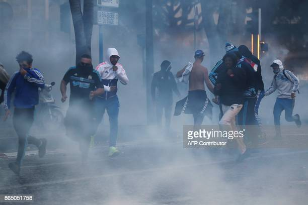 Marseille supporters run from tear gas as they clash with police a few hours prior to kick off of the French L1 football match between Marseille and...
