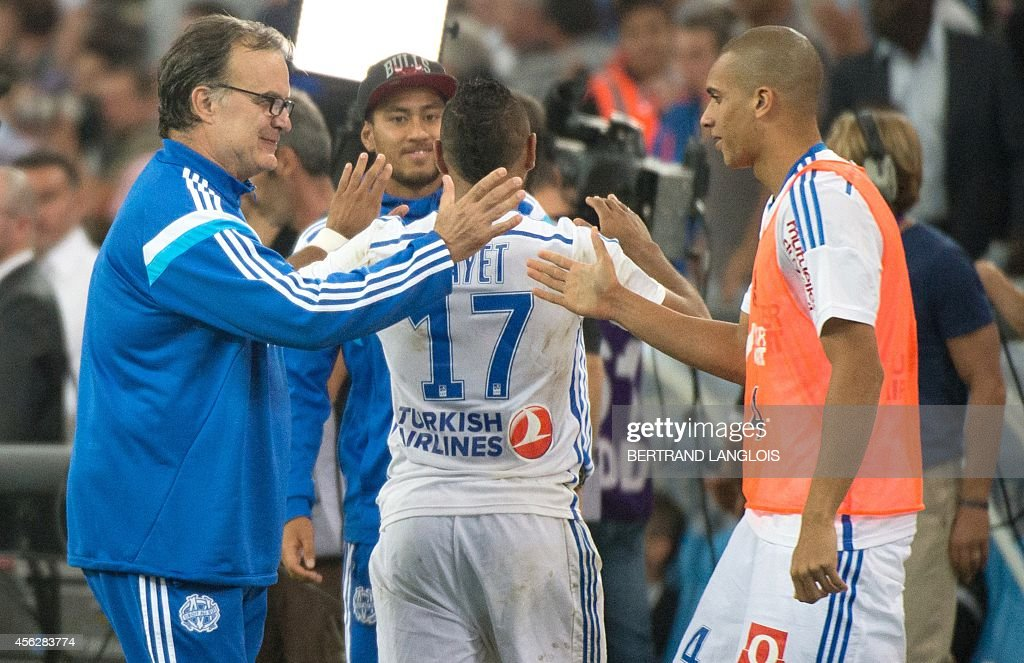 Marseille's Argentine head coach Marcelo Bielsa celebrates with Marseille's Brazilian defender Doria at the end of the French L1 football match...
