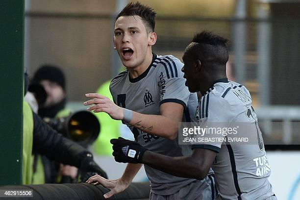 Marseille's Argentinian forward Lucas Ocampos celebrates after scoring with Marseille's French defender Benjamin Mendy during the French L1 football...