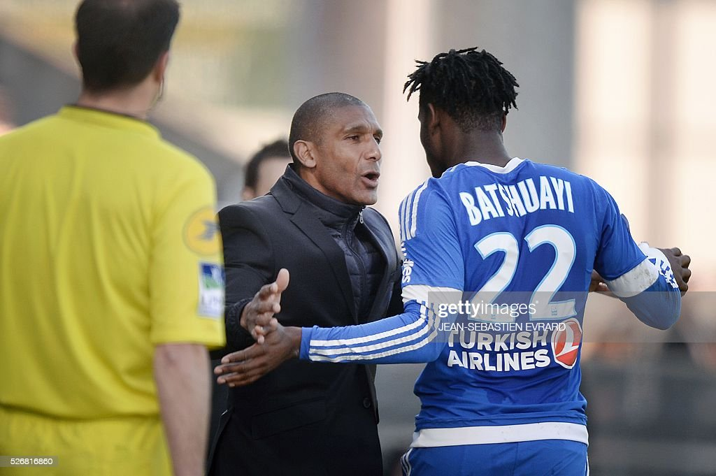 Marseille's Belgian forward Michy Batshuayi (R) is congratulated by Marseille's French assistant coach Franck Passi during the French L1 football match between Angers and Marseille on May 1, 2016 at the Jean Bouin stadium in Angers, western France.