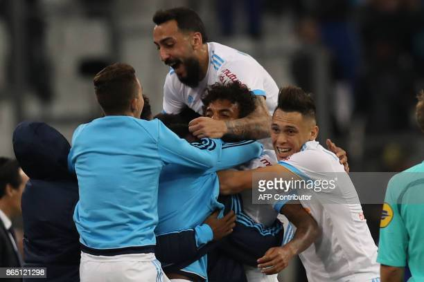 Marseille's Brazilian midfielder Luiz Gustavo is congratulated by teammates after scoring a goal during the French L1 football match between...