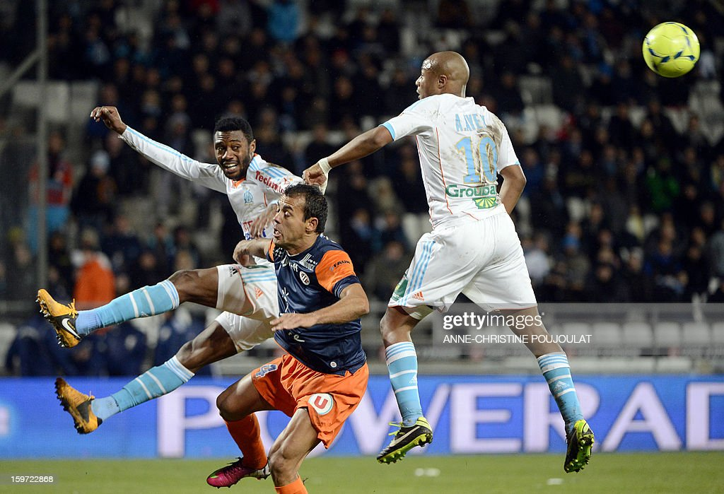 Marseille's Cameroonian defender Nicolas Nkoulou (L) and Marseille's Ghanaian forward Andre Ayew (R) vie with Montpellier's Brazilian defender Vitorino Hilton (C) during the French L1 football match Marseille (OM) vs Montpellier (MHSC) on January 19, 2013 at the Velodrome stadium in Marseille, southern France. AFP PHOTO / ANNE-CHRISTINE POUJOULAT