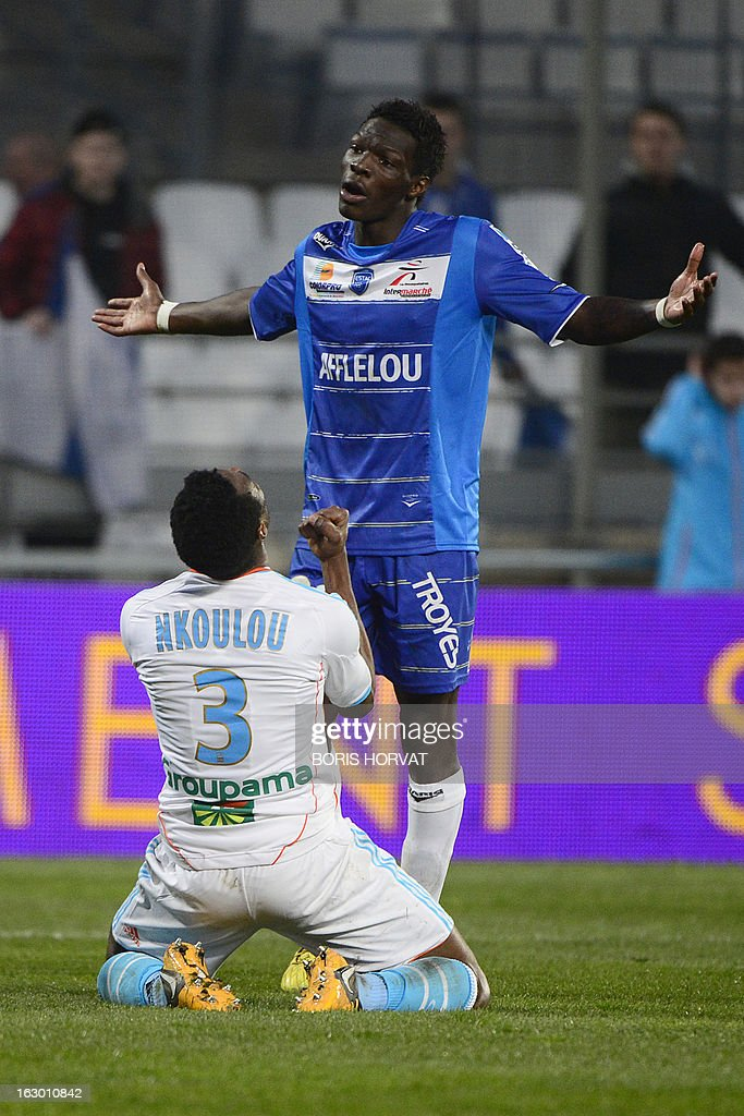 Marseille's Cameroonian defender Nicolas Nkoulou (bottom) celebrates after scoring, in front of Troyes' French defender Fabrice NSakala, during the French L1 football match Olympique of Marseille (OM) versus Troyes (ESTAC) at the Velodrome stadium in Marseille on March 3, 2013. AFP PHOTO / BORIS HORVAT