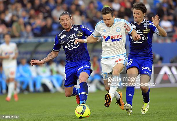 Marseille's Florian Thauvin vies with Bastia's French midfielder Mehdi Mostefa and Bastia's French midfielder Yannick Cahuzac during the L1 football...