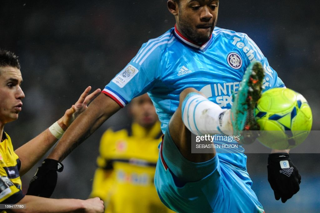 Marseille's forward Jordan Ayew (R) vies with Sochaux's defender Sebastien Corchia during the French L1 football match Sochaux (FCSM) vs Marseille (OM) at the August Bonal Stadium in Montbeliard, on January 13, 2013.