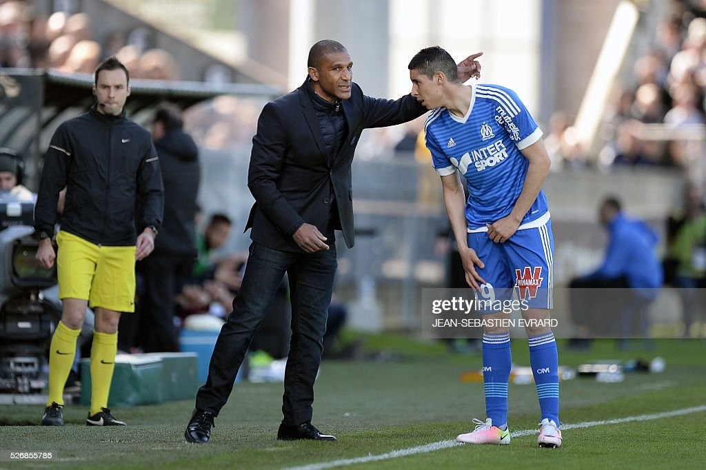Marseille's French assistant coach Franck Passi (L) gives instructions to Marseille's Moroccan midfielder Abdelaziz Barrada during the French L1 football match between Angers and Marseille on May 1, 2016 at the Jean Bouin stadium in Angers, western France.