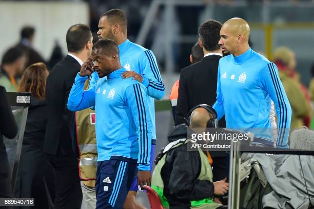 Marseille's French defender Patrice Evra is escorted off the pitch by teammates Portuguese defender Rolando and Brazilian defender Doria after an...