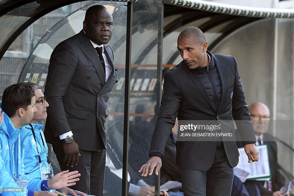 Marseille's French deputy coach Franck Passi (R) and former football player Basile Boli (3rdL) attend the French L1 football match between Angers and Marseille on May 1, 2016 at the Jean Bouin stadium in Angers, western France.