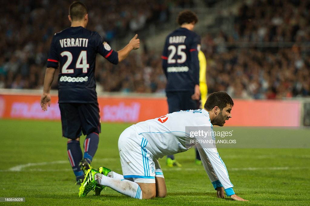 Marseille's French forward Andre-Pierre Gignac (down) is crouching next to Paris Saint-Germain's Italian midfielder Marco Verratti (L) during the French L1 football match Olympique de Marseille vs Paris Saint-Germain on October 6, 2013 at the Velodrome stadium in Marseille, southern France. AFP PHOTO / BERTRAND LANGLOIS