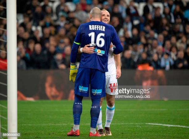 Marseille's French forward Valere Germain hugs SaintEtienne's French goalkeeper Stephane Ruffier during the French L1 football match Olympique de...