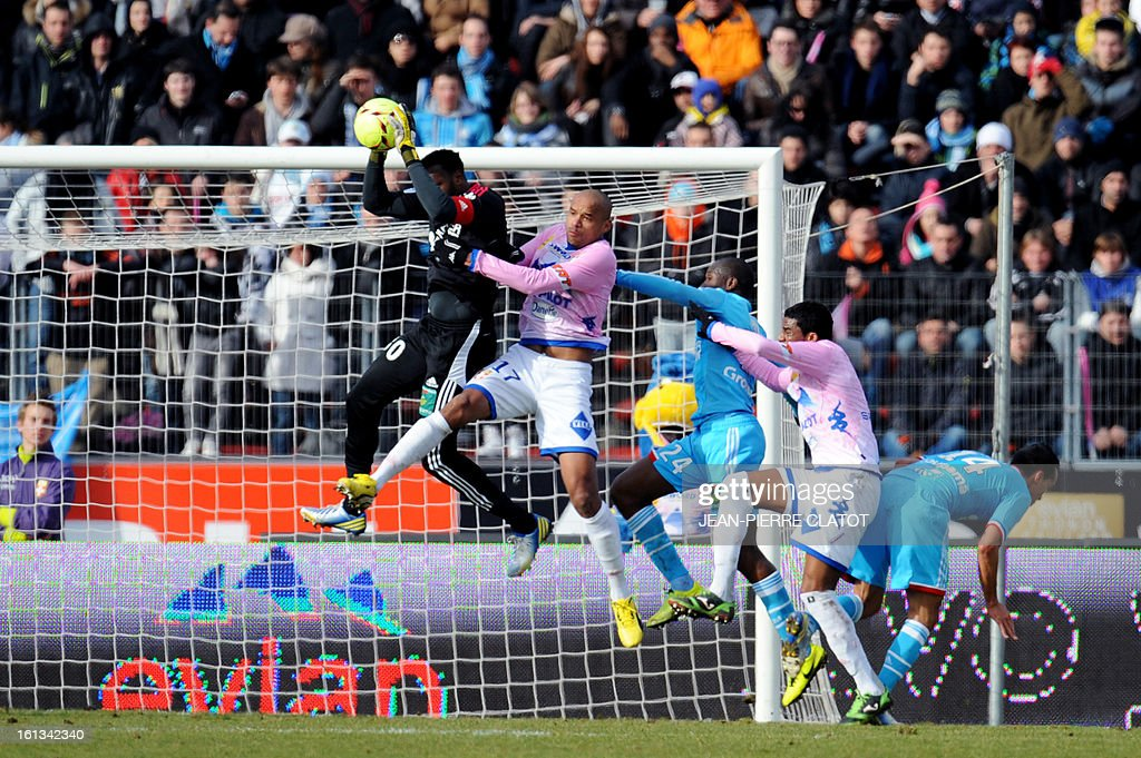 Marseille's French goalkeeper Steve Mandana (L) vies with Evian's French defender Aldo Angoula during their French L1 football match Evian (ETGFC) vs Marseille (OM) February 10, 2013 at the Parc des sports in Annecy, eastern France. AFP PHOTO / JEAN-PIERRE CLATOT