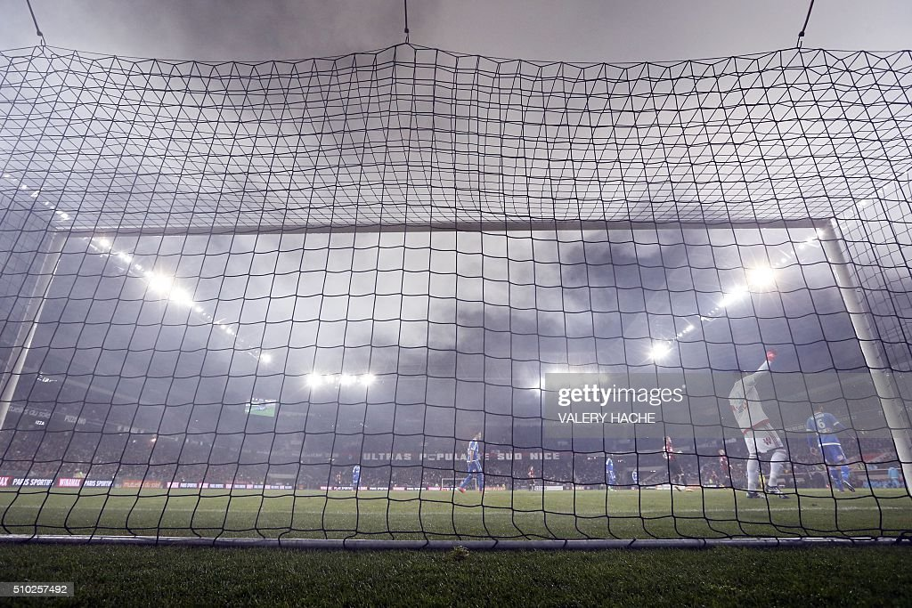 Marseille's French goalkeeper Steve Mandanda (2ndR) as smoke from smoke bombs come from the tribune during the French L1 football match Nice (OGC Nice) vs Marseille (OM) on February 14, 2016 at the 'Allianz Riviera' stadium in Nice, southeastern France. AFP PHOTO / VALERY HACHE / AFP / VALERY HACHE