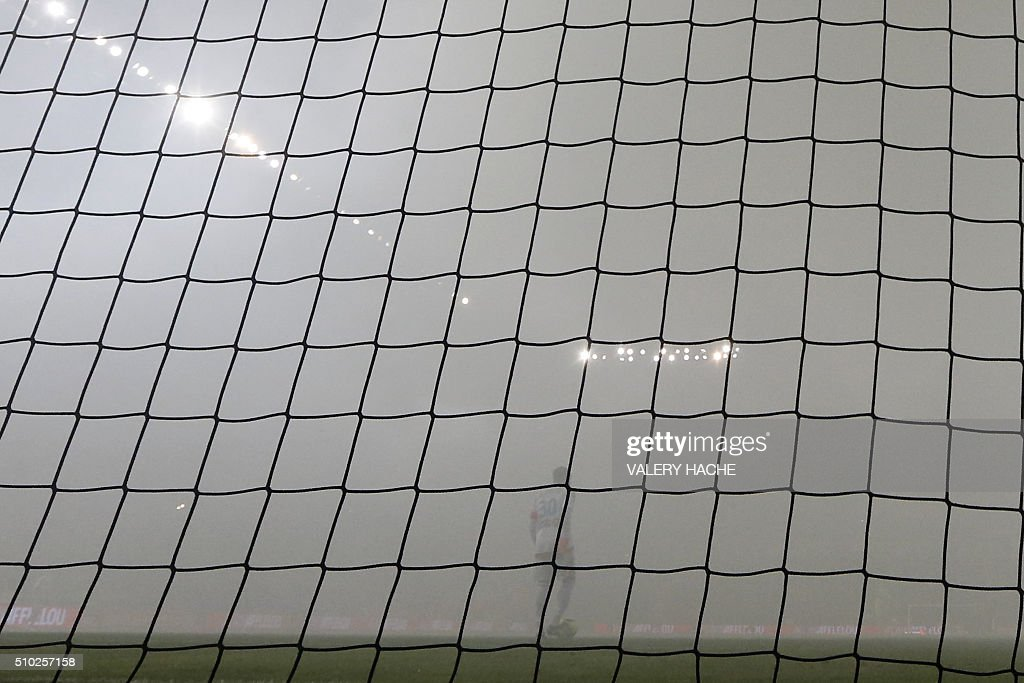 Marseille's French goalkeeper Steve Mandanda is pictured as the match is interrupted due to smoke bombs during the French L1 football match Nice (OGC Nice) vs Marseille (OM) on February 14, 2016 at the 'Allianz Riviera' stadium in Nice, southeastern France. AFP PHOTO / VALERY HACHE / AFP / VALERY HACHE
