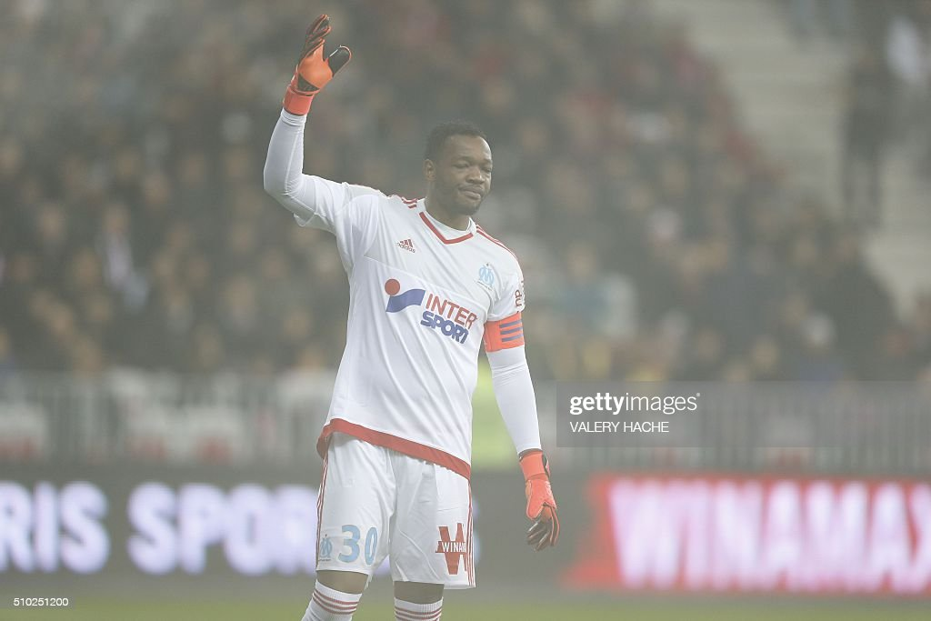 Marseille's French goalkeeper Steve Mandanda is seen through thick smoke from smoke bombs during the French L1 football match Nice (OGC Nice) vs Marseille (OM) on February 14, 2016 at the 'Allianz Riviera' stadium in Nice, southeastern France. AFP PHOTO / VALERY HACHE / AFP / VALERY HACHE