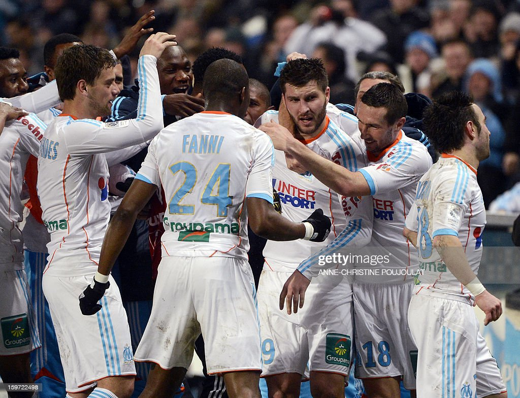 Marseille's French midfielder Andre Pierre Gignac (C) is congratulated by his teammates after scoring a goal during the French L1 football match Marseille (OM) vs Montpellier (MHSC) on January 19, 2013 at the Velodrome stadium in Marseille, southern France. AFP PHOTO / ANNE-CHRISTINE POUJOULAT