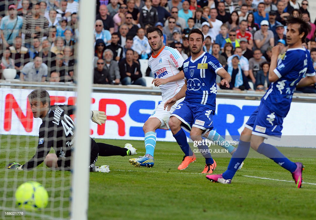 Marseille's French midfielder Andre Pierre Gignac scores a goal in front of Bastia's French goalkeeper Mickael Landreau and next to Bastia's French...