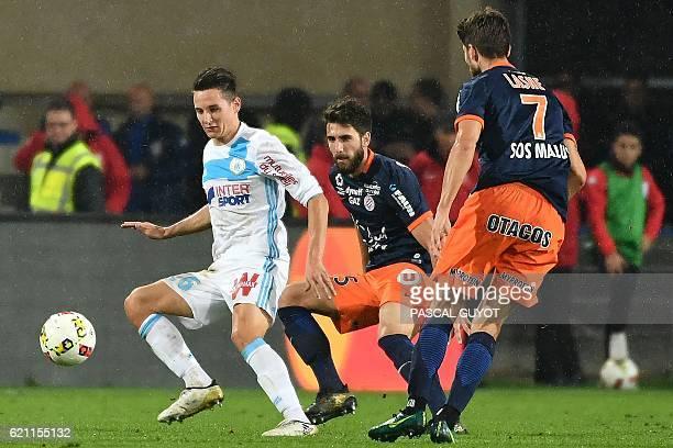 Marseille's French midfielder Florian Thauvin challenges Montpellier's French midfielder Paul Lasne and Montpellier's French defender Mathieu...