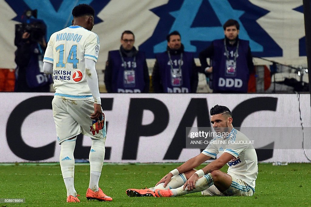 Marseille's French midfielder Georges-Kevin Nkoudou (L) and Marseille's French midfielder Remy Cabella (R) react at the end of the French L1 football match between Marseille and Paris-Saint-Germain on February 7, 2015 at the Velodrome stadium in Marseille, southern France. AFP PHOTO / ANNE-CHRISTINE POUJOULAT / AFP / ANNE-CHRISTINE POUJOULAT