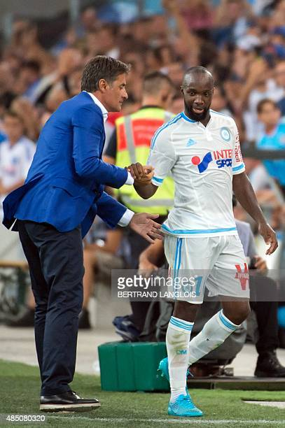 Marseille's French midfielder Lassana Diarra shakes hands with Marseille's Spanish head coach Jose Miguel Gonzalez Martin del Campo aka Michel during...