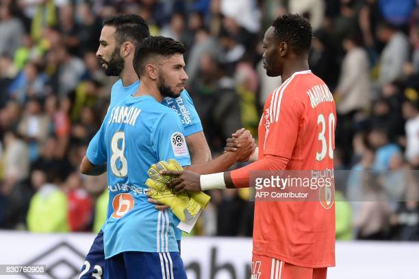 Marseille's French midfielder Morgan Sanson shakes hands with teammate Congolese goalkeeper Steve Mandanda at the end of the French L1 football match...