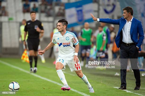 Marseille's French midfielder Remy Cabella runs with the ball as Marseille's Spanish head coach Jose Miguel Gonzalez Martin del Campo aka Michel...