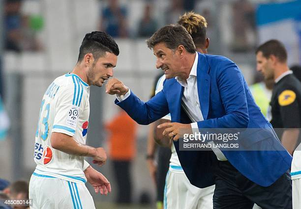 Marseille's French midfielder Remy Cabella speaks with Marseille's Spanish head coach Jose Miguel Gonzalez Martin del Campo aka Michel during the...