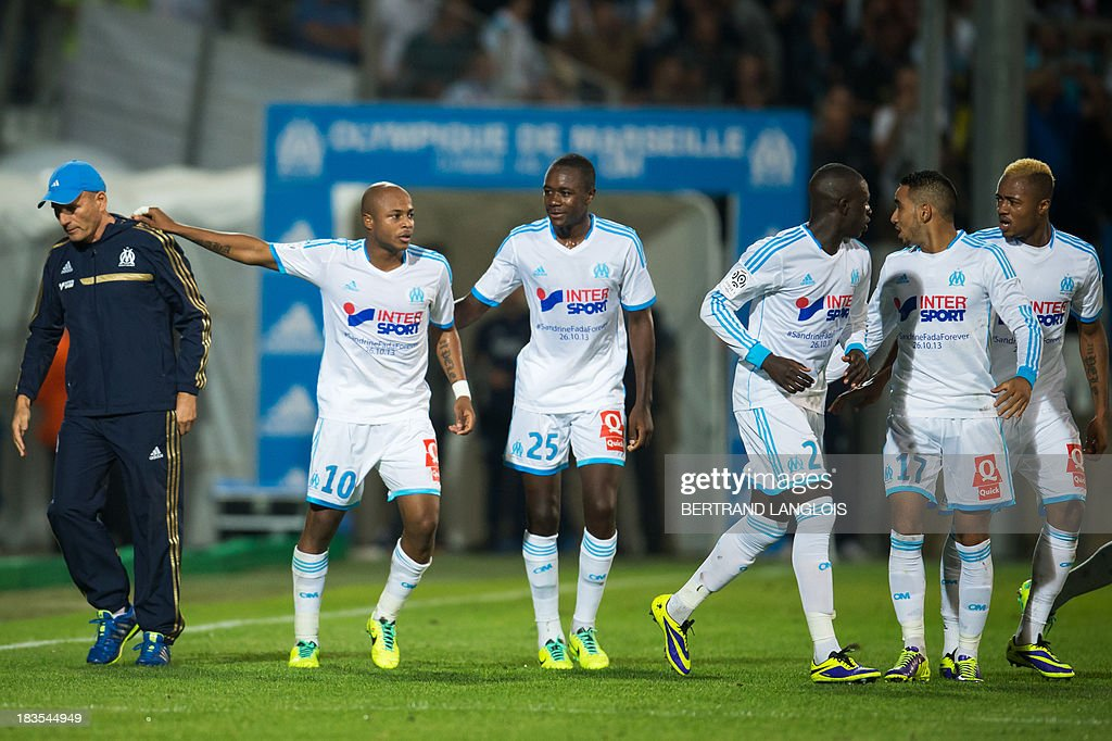 Marseille's Ghanaian forward Andre Ayew (2ndL) celebrates with team-mates and Marseille's French head coach Elie Baup (L) after scoring a penalty during the French L1 football match Olympique de Marseille vs Paris Saint-Germain on October 6, 2013 at the Velodrome stadium in Marseille, southern France. AFP PHOTO / BERTRAND LANGLOIS