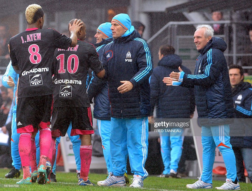 Marseille's Ghanaian forward Andre Ayew (2ndL ) is congratulated by his brother Jordan Ayew (L) and Marseille's French head coach Elie Baup (C) after scoring during the French L1 football match Brest vs Marseille at the Francis Le Ble stadium on December 2, 2012 in Brest, western France.
