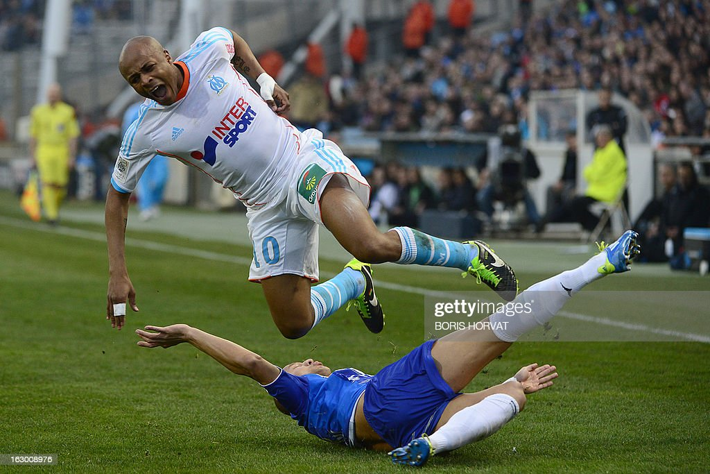 Marseille's Ghanaian forward Andre Ayew (top) jumps over Troyes' Brasilian midfielder Xavier Thiago who slid to the ground as the two vied for the ball during the French L1 football match Olympique of Marseille vs Troyes at the Velodrome Stadium in Marseille, on March 3, 2013.