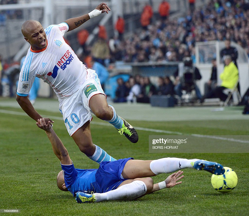 Marseille's Ghanaian forward Andre Ayew (top) vies for the ball with Troyes' Brasilian midfielder Xavier Thiago during the French L1 football match Olympique of Marseille vs Troyes at the Velodrome Stadium in Marseille, on March 3, 2013.