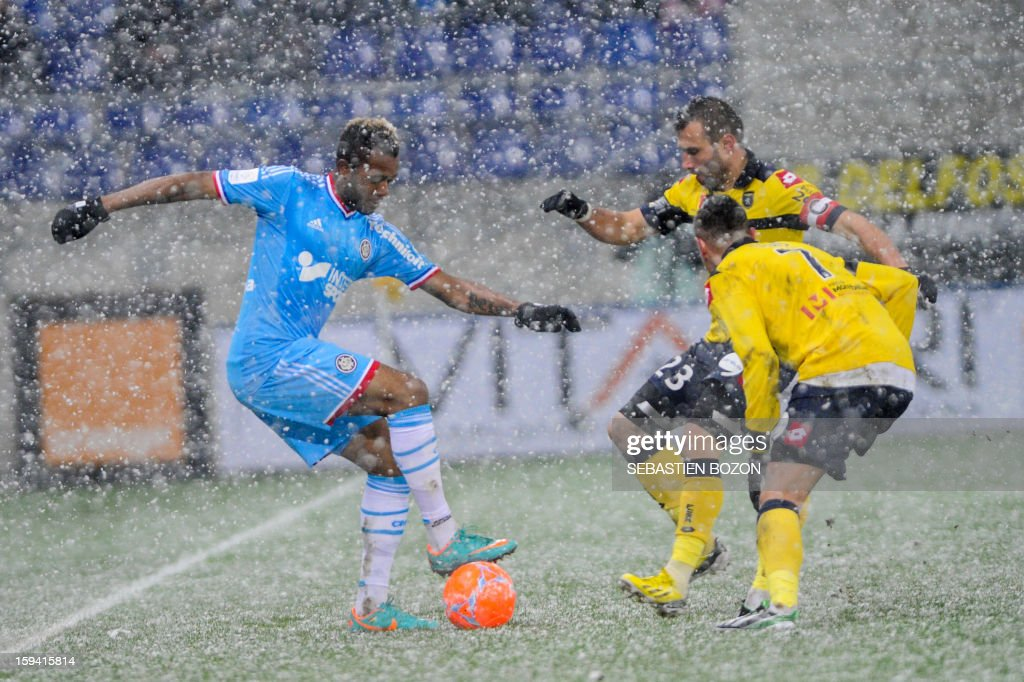 Marseille's Ghanaian forward Jordan Ayew (L) vies with Sochaux' French defender David Sauget (C,background) and Sochaux' Portugese forward Raphael Dias (R) during their French L1 football match Sochaux (FCSM) versus Marseille (OM) at the August Bonal Stadium in Montbeliard, on January 13, 2013AFP PHOTO / SEBASTIEN BOZON