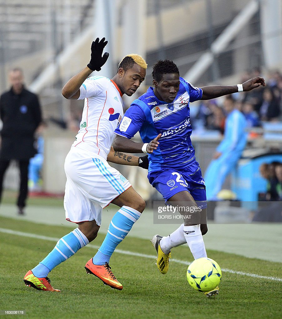 Marseille's Ghanaian forward Jordan Ayew (L) vies with Troyes' French defender Fabrice Nsakala during the French L1 football match Olympique of Marseille vs Troyes at the Velodrome Stadium in Marseille on March 3, 2013.