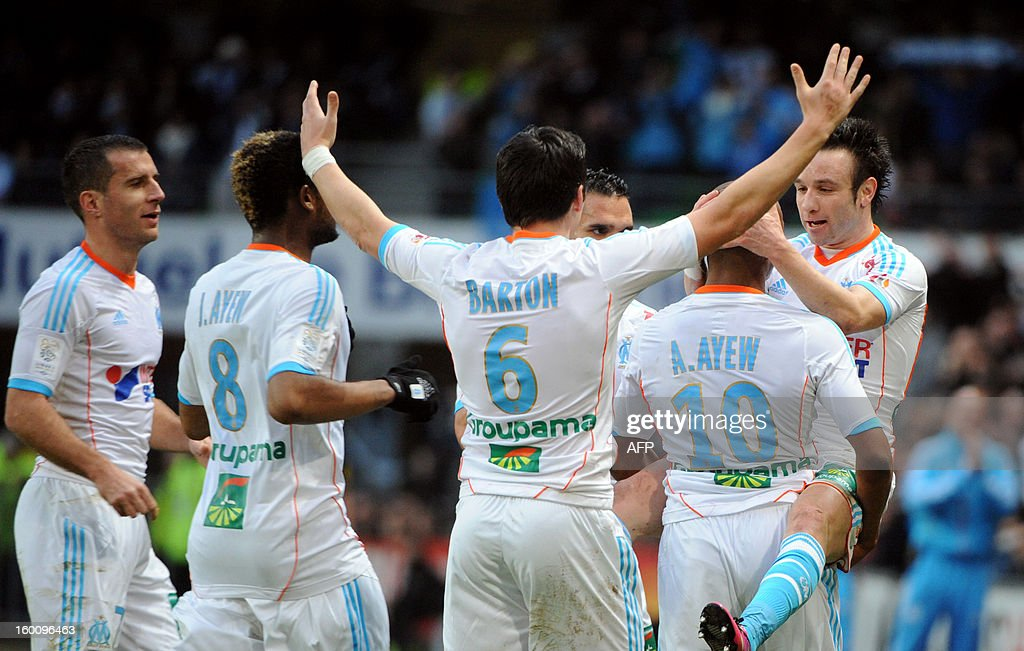 Marseille's Ghanaian midfielder Andre Ayew (2ndR) is congratulated by his teammates as he holds British midfielder Joey Barton (R) in his arms, after scoring a goal during the French L1 football match Stade Rennais FC vs. Evian (TG), on January 26, 2013 at the route de Lorient stadium in Rennes, western France.