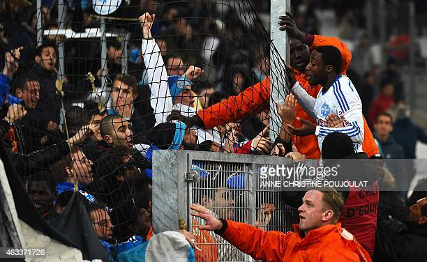 Marseille's Ivoirian defender Brice Dja Djedje celebrates with Marseille's supporters after his teammate Ghanaian forward Andre Ayew scored during...