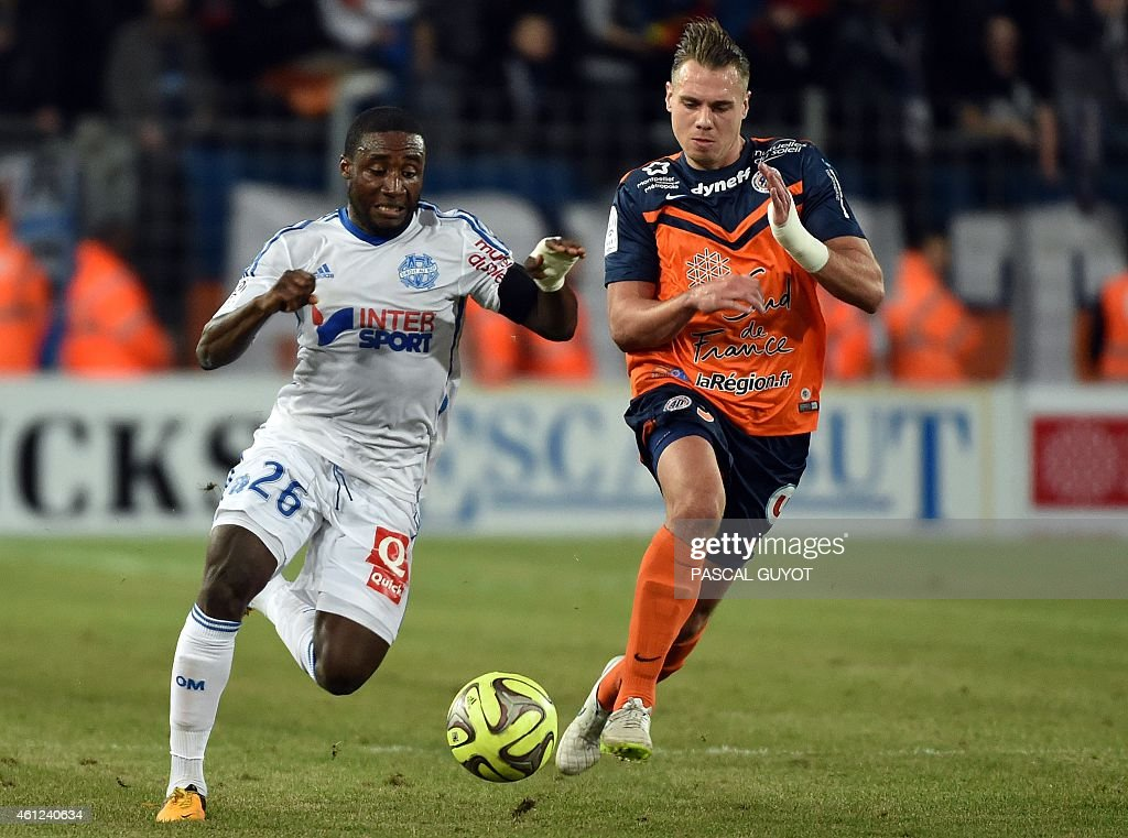 Marseille's Ivorian defender Brice Dja Djedje (L) challenges Montpellier's French forward Kevin Berigaud (R) during the French L1 football match between Montpellier and Marseille at the La Mosson Stadium in Montpellier, southern France, on January 9, 2015. AFP PHOTO / PASCAL GUYOT