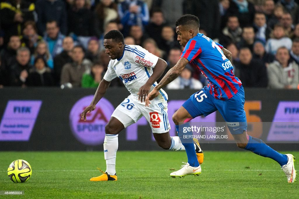 Marseille's Ivorian defender Brice Dja Djedje (L) vies with Caen's French Beninese defender Emmanuel Imorou during the French L1 football match between Marseille (OM) and Caen (SMC) on February 27, 2015 at the Velodrome stadium in Marseille, southern France.