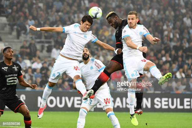 Marseille's Japanese defender Hiroki Sakai fights for the ball with Rennes' French defender Joris Gnagnon and Marseille's French midfielder Gregory...