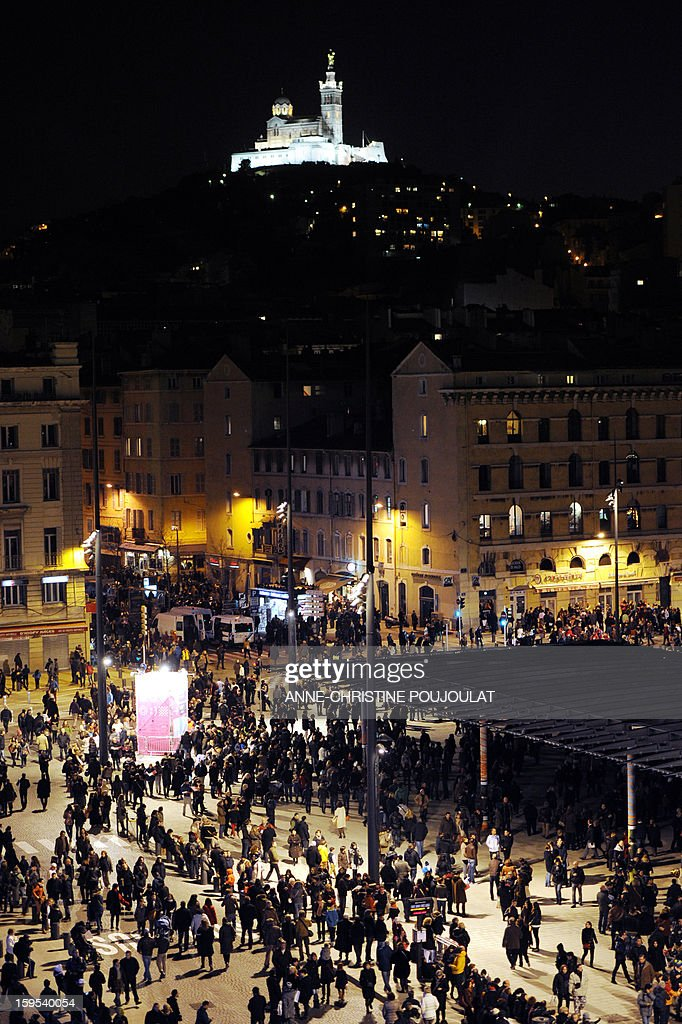Marseille's Notre-Dame de la Garde basilica, emblem of the city is enlighted as people gather on January 12, 2013 at the Vieux-Port harbour in Marseille, southern France, to attend the opening festivities marking Marseille as the 2013 European Capital of Culture.
