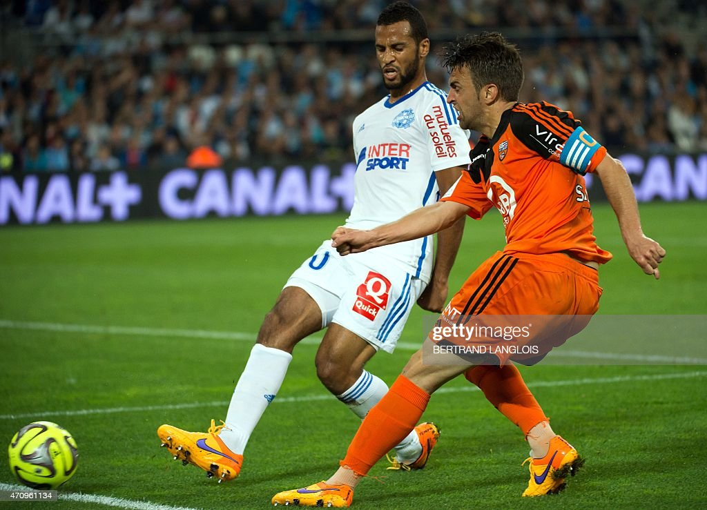 Marseille's Togolese midfielder Jacques-<a gi-track='captionPersonalityLinkClicked' href=/galleries/search?phrase=Alaixys+Romao&family=editorial&specificpeople=554325 ng-click='$event.stopPropagation()'>Alaixys Romao</a> (L) vies with Lorient's French midfielder Yann Jouffre during the French L1 football match between Marseille and Lorient on April 24, 2015 at the Velodrome stadium in Marseille, southern France. AFP PHOTO / BERTRAND LANGLOIS