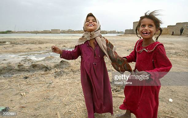Marsh Arab children laugh near a marsh area that is slowly being reflooded with water June 2 2003 in Suk Shuykuh Iraq The Marsh Arabs have inhabited...