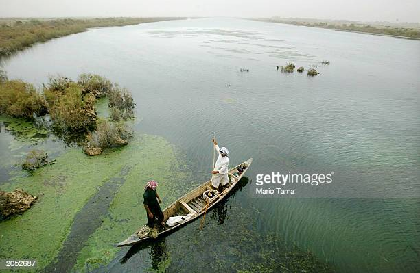 Marsh Arab guides his boat through a marsh area that is slowly being reflooded with water June 3 2003 in AlFohud Iraq The Marsh Arabs have inhabited...
