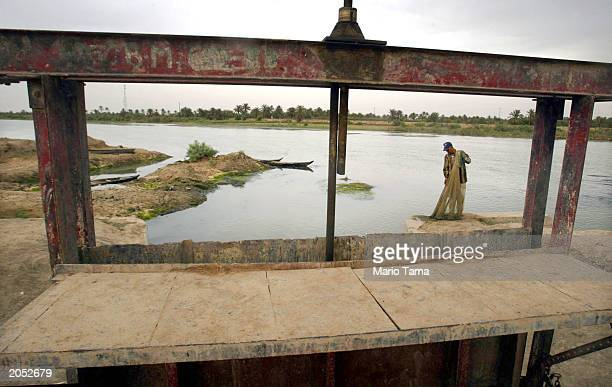 Marsh Arab is framed by a dam gate which was reopened in a marsh area that is slowly being reflooded with water June 2 2003 in Suk Shuykuh Iraq The...