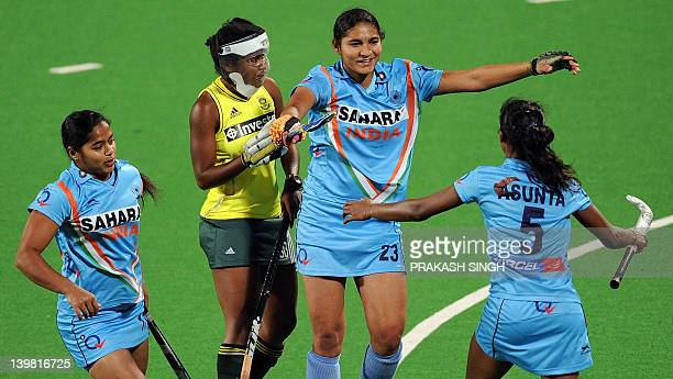 Marsha Marescia of South Africa vies for the ball with India team players during the women's field hockey final qualifying position match between...