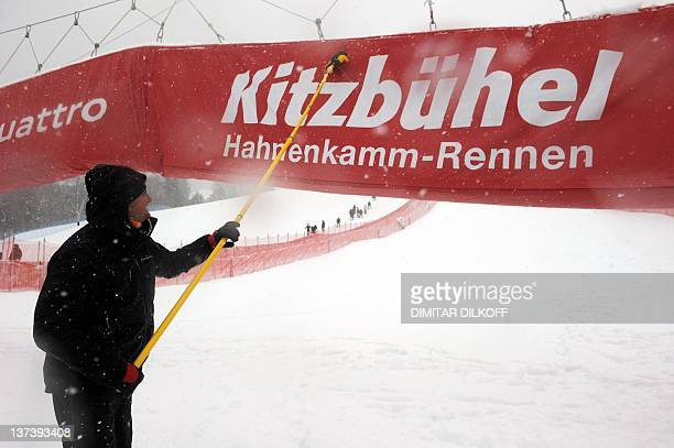 A marshal cleans the finish line banner of the Streif course in Kitzbuehel on January 20 2012 as the men's World Cup superG event scheduled today has...