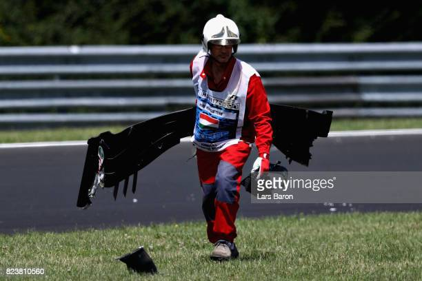 A marshal removes the front wing of Antonio Giovinazzi of Italy and Haas F1 from the circuit during practice for the Formula One Grand Prix of...