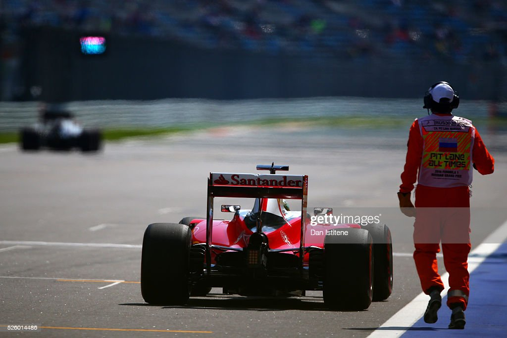 A marshal runs to retrieve Sebastian Vettel of Germany driving the (5) Scuderia Ferrari SF16-H Ferrari 059/5 turbo (Shell GP) after he stopped on the start finish straight during practice for the Formula One Grand Prix of Russia at Sochi Autodrom on April 29, 2016 in Sochi, Russia.