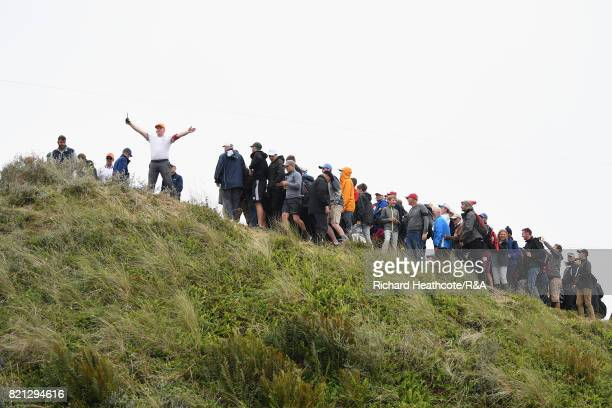 A marshal signals his position from the top of a dune as Jordan Spieth of the United States prepares to play his third shot from the practice range...
