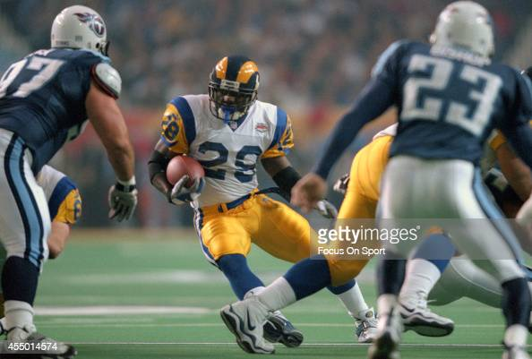 Marshall Faulk of St Louis Rams carries the ball against the Tennessee Titans during Super Bowl XXXIV at the Georgia Dome on January 30 2000 in...
