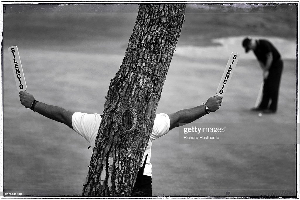 A marshall holds up silence plaques as a player putts on the 15th green during the second round of the Open de Espana at Parador de El Saler on April...